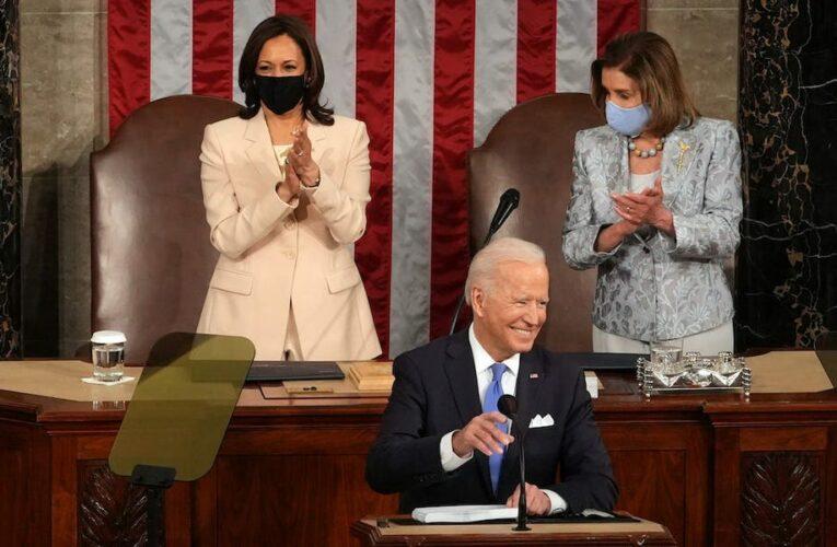 Elizabeth Warren fist-pumps and Joe Manchin takes notes during Biden's first joint address to Congress
